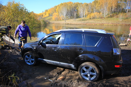 SUV got stuck in the mud and trying to go out in the autumn forest. People try to help. Reklamní fotografie - 54010054