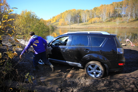 SUV got stuck in the mud and trying to go out in the autumn forest. People try to help.