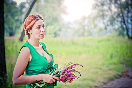 woman back view: Romantic red-haired young woman in green long dress Carrying Bouquet Of Flowers.