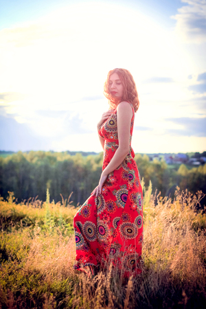 turn away: portrait of beautiful red-haired curly girl posing outdoors