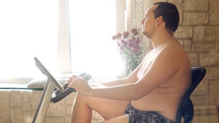 simulator: Overweight man exercising on bike simulator at home