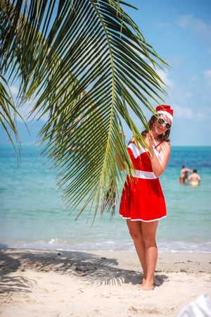 stands: Cute blonde woman in red dress, sunglasses and santa hat stands at palm tree on exotic tropical beach. Holiday concept for New Years Cards. Koh Samui.