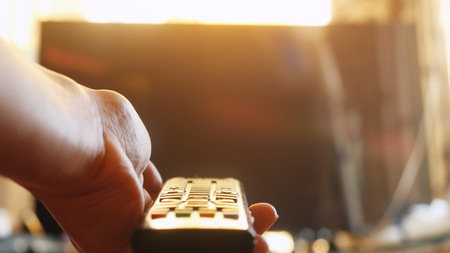 Close up of womans hand with a television remote control at sunset time