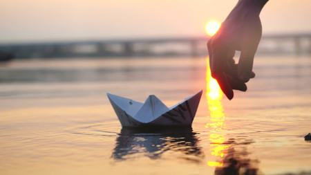 Mans hand putted paper boat on the water and pushing it away during beautiful sunset with reflection sun in the sea