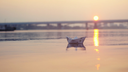 paper boat on the water during beautiful sunset with reflection sun in sea Stock Photo