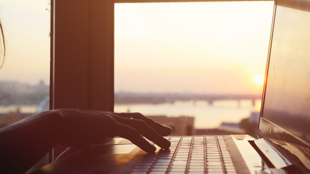 flare up: Close up of womans hand typing on laptops keyboard during sunset with sun lense flare effects. Stock Photo