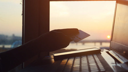 Online mobile payment method using mobile smart phone and credit card. Woman shopping with her laptop on blurred city background during amazing sunset and beautiful sun lense flare effects