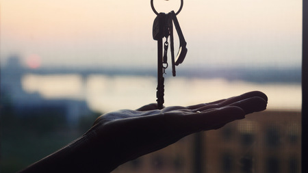 Hand holding three metal keys on construction site during sunset background, Industrial backdrop, Building concept Stock Photo