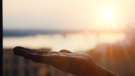 Female hand on blurred city background during beautiful sunset with lense flare effects