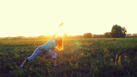 Beautiful young brunette woman doing yoga exercise on the field during amazing sunset.