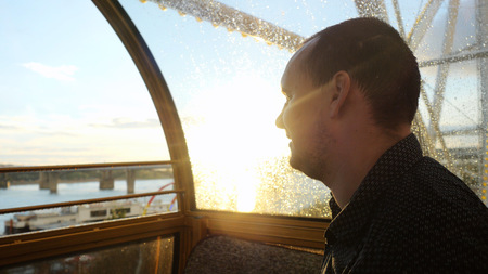 french ethnicity: Young handsome man sits in a ferris wheel looking at during beautiful sunset and sun flare effects.