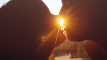 Romantic young beautiful couple in love looking each other and kissing on a sunset with sun shining bright behind them on a horizon. Stock Photo