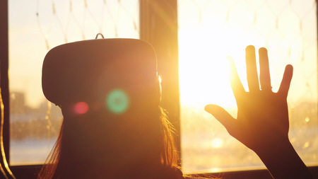 uses: Young woman uses a virtual reality glasses at home during sunset with city background from the window and beautiful lense flare effects
