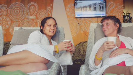 luxury house: Two pretty women daughter and mom are relaxing in a spa center, talking and drink cup of tea