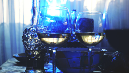 Glass glasses on a table in a restaurant, banquet table, glasses of wine stage blue lighting. Reklamní fotografie