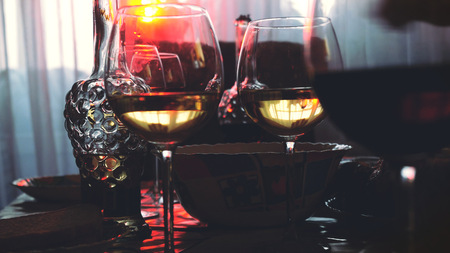 Glass glasses on a table in a restaurant, banquet table, glasses of wine stage golden lighting.