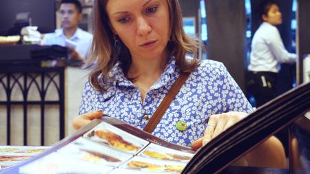 turning the page: Young pretty woman reading menu in cafe Stock Photo
