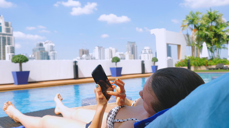 Young woman using smartphone sends sms on sunbed by pool on urban architecture background Reklamní fotografie