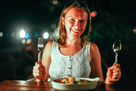 Young cheerful smiling woman holding spoon and fork in an outdoor cafe at the sea on beautiful bokeh lights