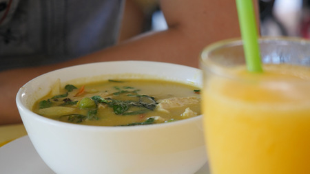 favorite soup: Man eating Thai green curry soup at an outdoor restaurant