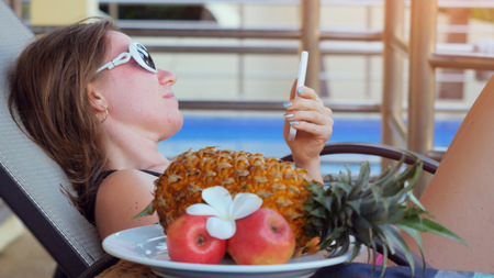 Young woman wearing sunglasses lying on a sunbed uses smartphone next to the swimming pool and eats fruits on summer holidays while vacation