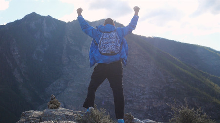 Hiker with backpack standing on top of a mountain with hands rised up. Back view, travel and recreation.