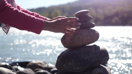 Female hands putting pebble stack next to the mountain river on sunny day