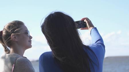 Fun Teen Girls take Selfie Vacation Photos by the sea.
