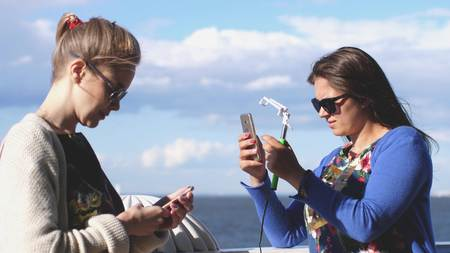 Woman takes photos her friend with mobile phone Vacation Photos by the sea. Stock Photo