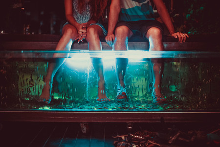 Couple enjoying with Fish Spa pedicure, foot bath using fish the eat dead skin.