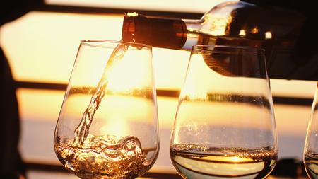 Witte wijn in glazen gieten bij prachtige zonsondergang aan zee in strandcafé. Stockfoto