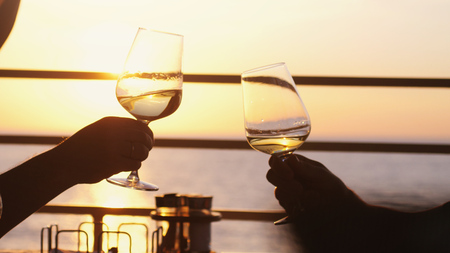 People holding glass of wine, making a toast over sunset. Party outdoors. Enjoying time together.