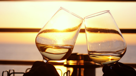 People holding glass of wine, making a toast over sunset. Friends drinking white wine, toasting. Clink. Party outdoors. Enjoying time together.