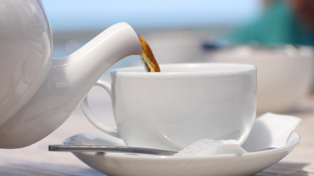 White teapot pouring tea into cup in beach cafe by the sea with sunlight. 写真素材