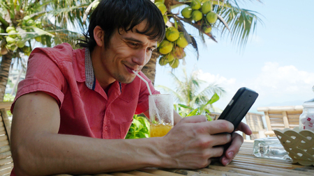 Young handsome joyful man uses smart phone while having drinks cocktail in a tropical location with palm trees in the back. Stock Photo