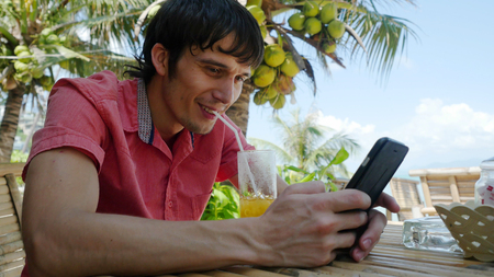 Young handsome happy man uses smart phone while having drinks cocktail in a tropical location with palm trees in the back. Stock Photo