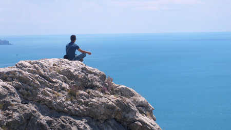 Man on the edge meditating, sits on top of the rock against a background of blue sea and the sky