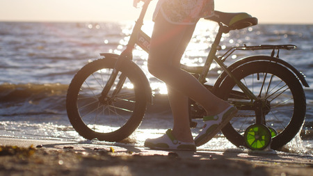 Close up of the child walks along the beach with a bicycle during sunset