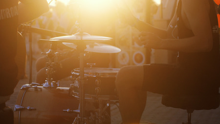Man playing drums on promenade at amazing golden sunset and lens flare effects