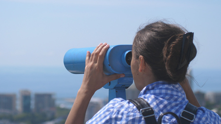 Tourist looking through binoculars at Sochi. Young woman with backpack looking through binoculars from a tower high above city on sunny day Stok Fotoğraf