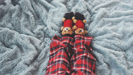 Feet at home in bed dressed socks with cute teddy bears and in pajamas. top of view Stock fotó