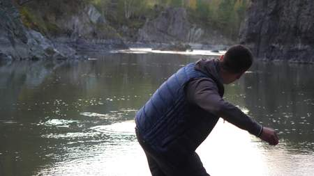Young man throwing stones in the mountain river