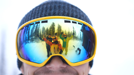 Portrait of smiling man in the blue skiing glasses in deep beautiful forest and cheerful friends waving their hands and are reflected in his glasses. Close up