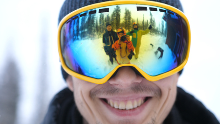 Portrait of smiling happy man in skiing glasses in deep beautiful forest and cheerful friends waving their hands and reflected in his glasses. Close up
