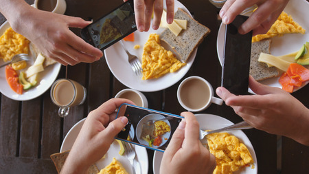 Top view of a group of friends having breakfast in a cafe at wooden table, taking picture of omelette, toasts and coffee with mobile phone. Stock Photo