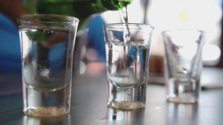 Pouring sake into glasses in japanese cafe an outdoor