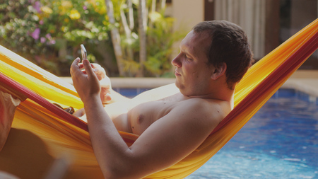 Fat sad man with bare chest lies in hammock uses mobile phone by swimming pool. Banco de Imagens