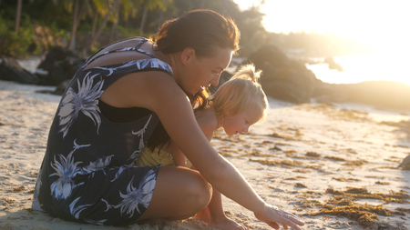 Little cute girl baby and young mother sitting at tropical beach during beautiful sunset Stock Photo