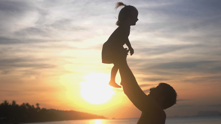 Father throwing up his happy baby daughter in the air at beautiful sunset on the beach