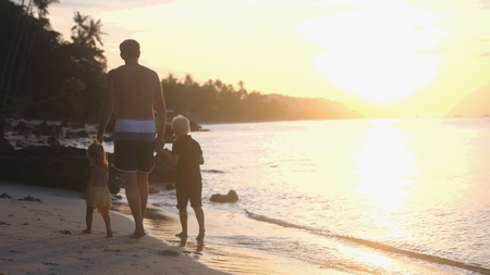 Father with children walking on the beach. Dad holding childrens hands at beautiful sunset. Travel holiday concept